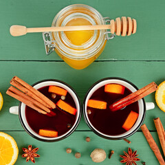 Mulled wine in white rustic mugs with spices and citrus fruit.