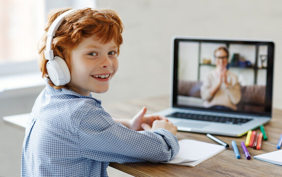 Cheerful boy during online lesson at home.