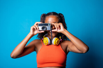 Young beautiful black woman taking pictures with retro vintage photo camera on blue background - Diverse female isolated studio shot holding camera