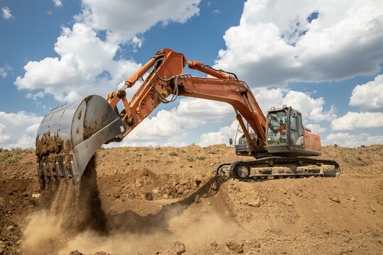 A large industrial excavator work on the construction site.  Cloudy sky