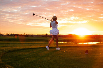 Lady Play Golf With Sunset Background .