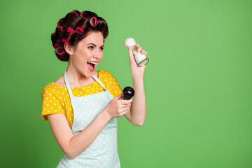 Photo of cute pretty excited young girl roller hairstyle hold pepper shaker salt bottle open mouth free time pretend have maracas wear dotted apron shirt isolated green color background
