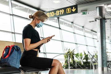 Young woman is a wearing prevention mask in an airport during flight awaiting