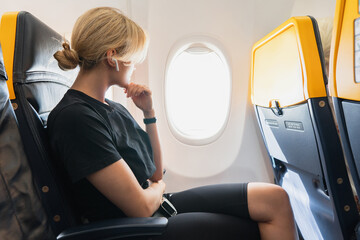 Woman listening music inside an airplane during her flight