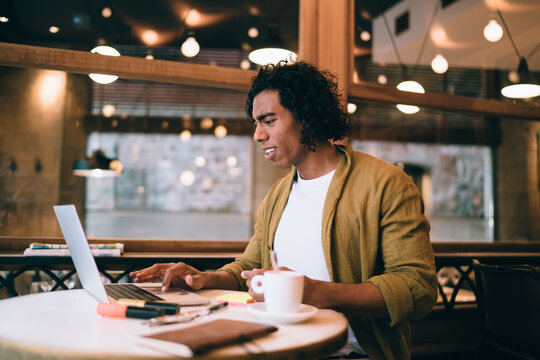 Confused male freelancer working on laptop in cafe