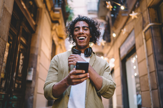Happy man using smartphone and headphones on narrow street