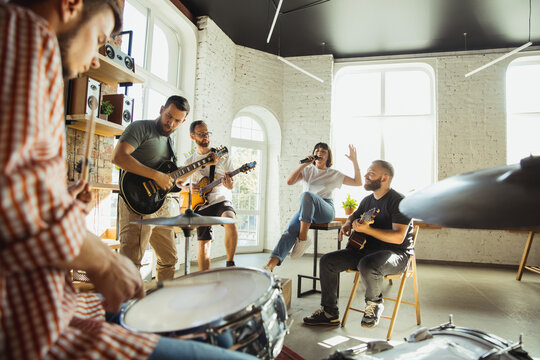 Inspiration. Musician band jamming together in art workplace with instruments. Caucasian men and women, musicians, playing and singing together. Concept of music, hobby, emotions, art occupation.