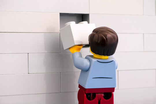 Tambov, Russian Federation - June 07, 2020 Lego man minifigure with gray brick finishing a wall