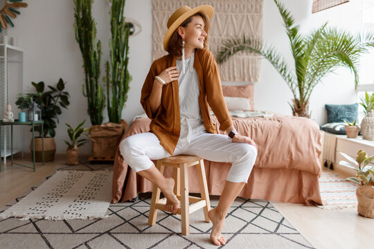 Fashionable image of happy woman in straw hat posing over bohemian interior background. Straw hat , linen  closes. Natural make up. Full lengt.