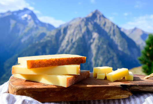Cheese collection, French comte, beaufort or abondance cow milk cheese served outdoor with Alps mountains peaks on background