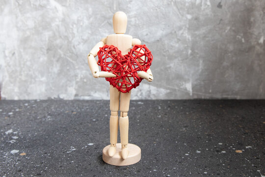 Wooden mannequin with red rattan heart.