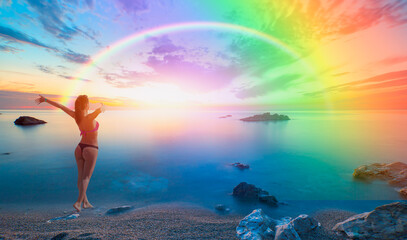 Happy slim girl in red and black bikini with raised up arms on the seashore -  Long exposure image of Dramatic sky and seascape with rock and amazing rainbow-  - Alanya, Turkey