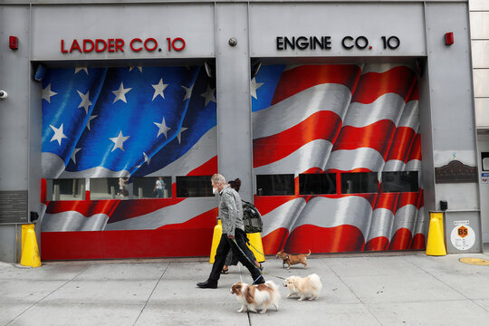 A man wearing a protective face mask walks his dogs, two days before the 19th anniversary of the 9/11 attacks, amid the coronavirus disease (COVID-19) pandemic, in the lower section Manhattan, New York City