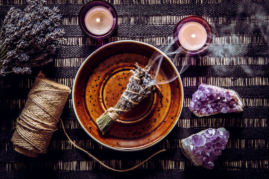 Homemade herbal lavender (lavendula) smudge stick smoldering on white plate with candles and amethyst crystal clusters for decoration. Spiritual home cleansing concept.