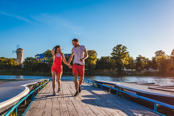 Young man and woman running along summer river dock. Couple having fun at sunset holding hands. People relaxing Wall mural