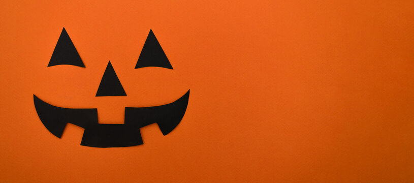 Black eyes,nose and mouth of black paper on an orange background.Happy Halloween concept.Copy space for text