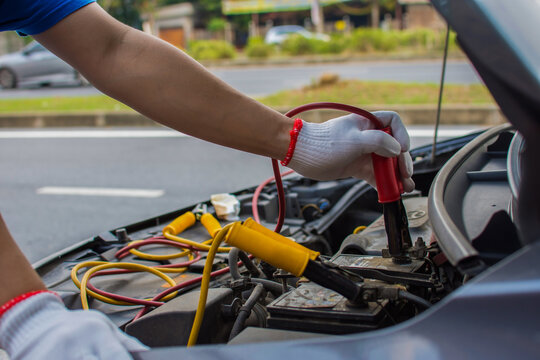 The technician uses a booster cable to connect the dead battery. Electric vehicle battery charging via jumper cable