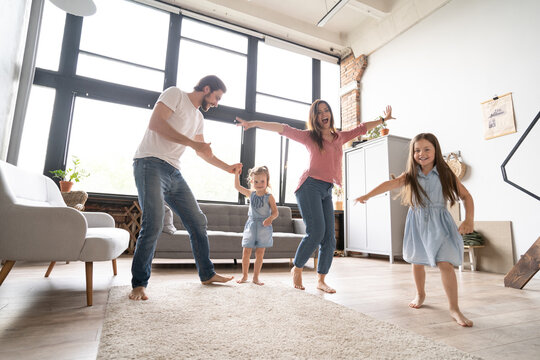 happy family mother father and child daughter dancing at home
