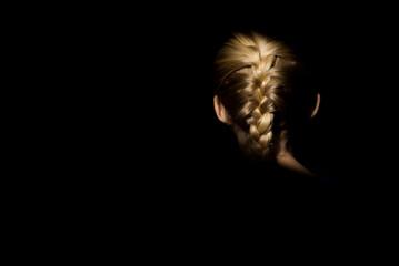 Blonde girl braid in light with dark background
