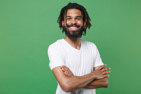 Smiling cheerful funny young african american man guy 20s wearing white casual t-shirt posing holding hands folded crossed looking camera isolated on green color wall background studio portrait.