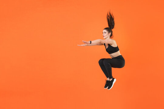 Full length portrait of young fitness sporty woman 20s wearing black sportswear training jumping doing exercise squatting stretching hands looking aside isolated on orange color background studio.