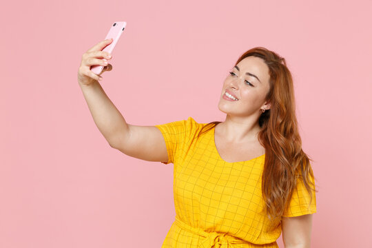 Smiling beautiful young redhead plus size body positive female woman girl 20s in yellow dress posing doing selfie shot on mobile phone isolated on pastel pink color wall background studio portrait.