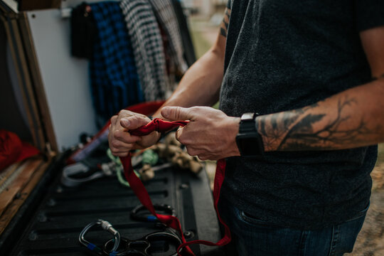 Man tightening knots on climbing ropes