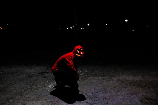 A Man Wearing A Red Hoodie With Red Glowing Mask Sitting On The Ground