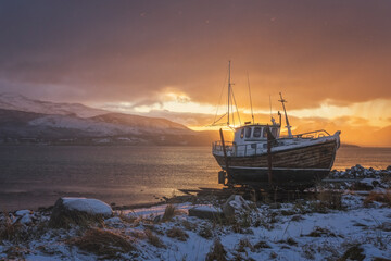 Norwegian wooden boat beached at sunset with snow