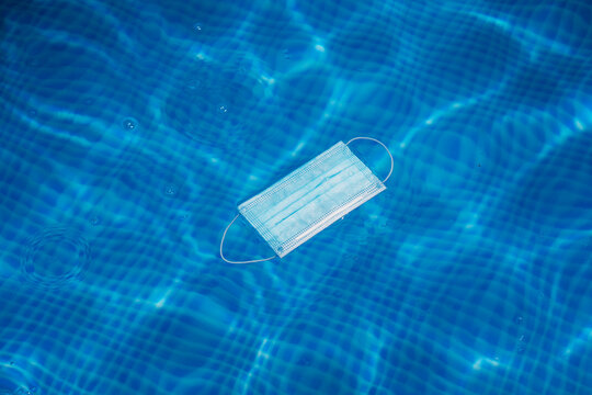 Mask floating on pool water during Covid pandemic.