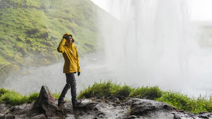 Happy female hiker in a bright rain coat behind powerful waterfall