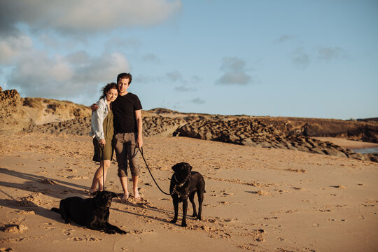 Millennial couple standing at beach with two black labradors