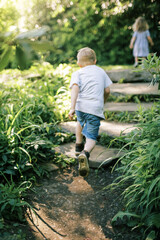 Two kids running up stone steps in a nature park