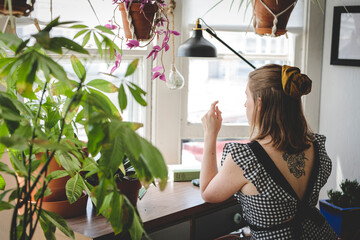Young woman sits at desk with plants and books