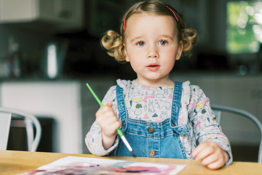 Portrait of girl painting with watercolors at table