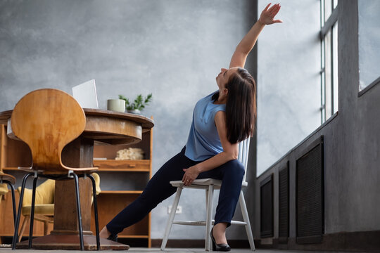 Young woman practicing yoga, stretching in Extended Side Angle exercise, Utthita parsvakonasana pose, working out at home sitting on chair.