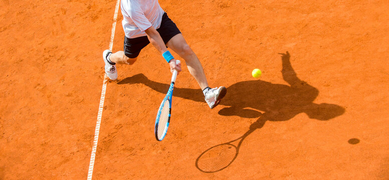 Old male tennis player in action on the court on a sunny day