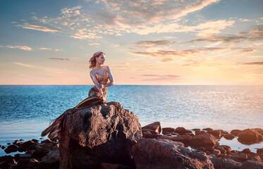 Sadness mermaid, nixie, water nymph sitting on stone. Sea, sunset view