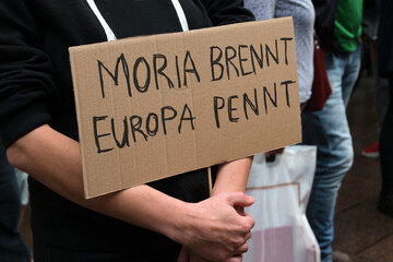 Demonstrator holds a cardboard with German text Moria brennt, Europa pennt (Moria is burning, Europe is sleeping), demonstration in Lubeck for accommodation of refugees after fire in the Greek camp