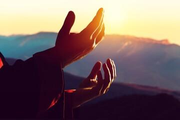 Human male hand praying outdoor