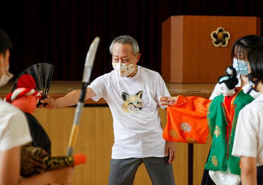 Kanjuro Kiritake, a Bunraku puppeteer, gives lessons in traditional puppet drama to students at Kozu elementary school, amid the coronavirus disease (COVID-19) outbreak, in Osaka