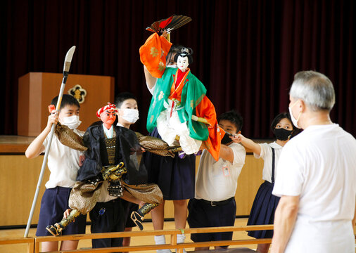 Kozu elementary school students perform a traditional puppet drama in front of Kanjuro Kiritake, a Bunraku puppeteer, during a class in Osaka