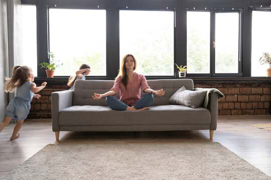Calm woman concentrating on yoga exercises on couch at home while two noisy kids laughing, running, catching each other, having fun, stress reduction concept.