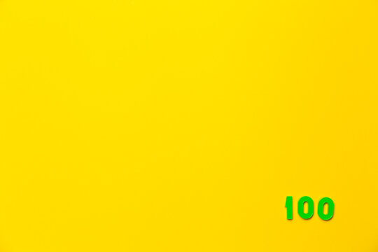 A green plastic toy number hundred is located in the lower right corner on a yellow background