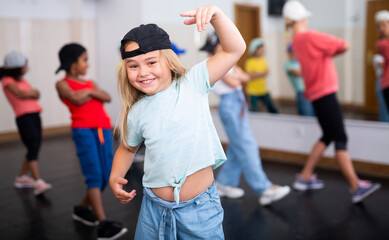 Portrait of emotional girl doing hip hop movements during group class in dance studio