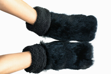 women hands wearing black fur mittens isolated on white background