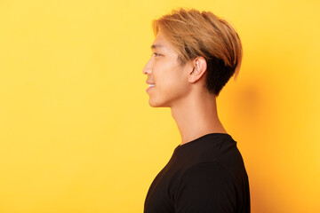 Profile of stylish handsome asian guy with fair hair looking left and smiling, standing over yellow...