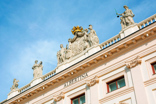 vienna, austria - OCT 17, 2019: side view of albertina museum building. logo on the wall. statues with crown on the roof. sunny afternoon with blue sky