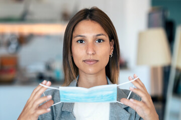 Young beautiful woman putting on an hygienic mask to prevent others from a virus while looking at camera in the home.