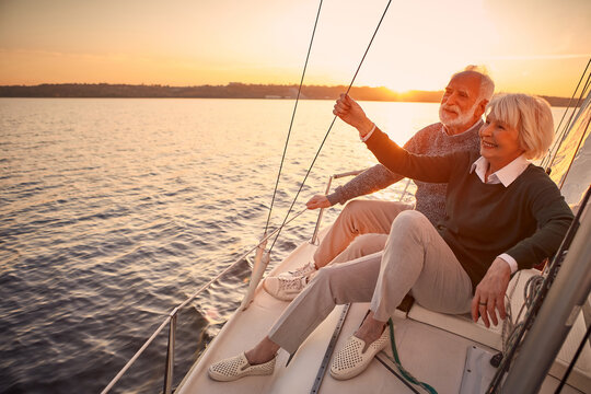 Enjoying luxury life. Beautiful happy senior couple in love relaxing on the side of sailboat or yacht deck floating in sea at sunset, looking at amazing evening view